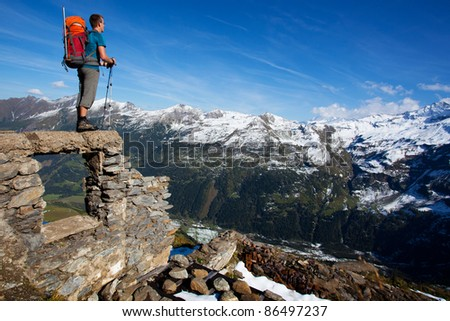 Young man with backpack enjoying mountain view - stock photo