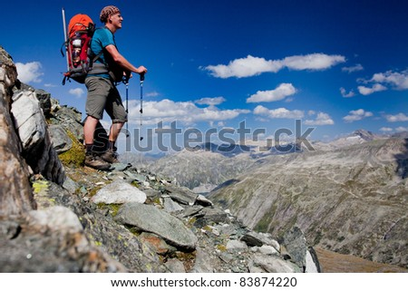 Young man with backpack on a mountain hike - stock photo