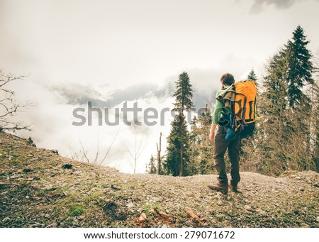Young Man with backpack relaxing outdoor with foggy mountains on background Lifestyle Travel concept Summer vacations - stock photo