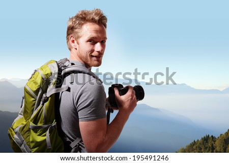 Young man with backpack taking a photo on the top of mountains, caucasian - stock photo