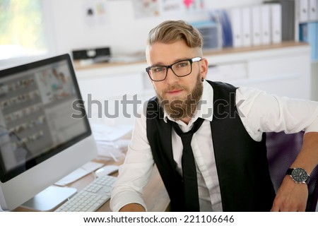 Young man with beard and eyeglasses in office - stock photo