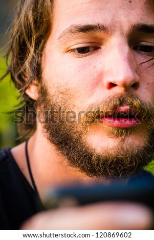 young man with beard and mobilephone - stock photo