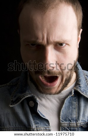 young man with beard and mustache screaming (black background)
