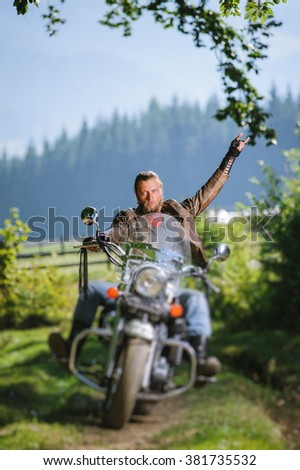 young man with beard driving his cruiser motorcycle in the forest and giving the devil horns gesture. Man is wearing leather jacket and blue jeans. Tilt shift lens blur effect - stock photo