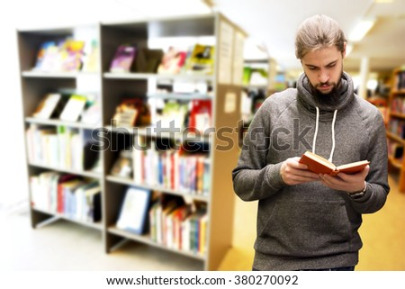 Young man with beard reading a book in library