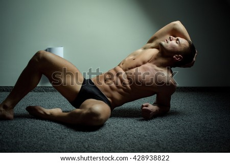 Young man with beautiful muscular torso in underwear lying on floor - stock photo