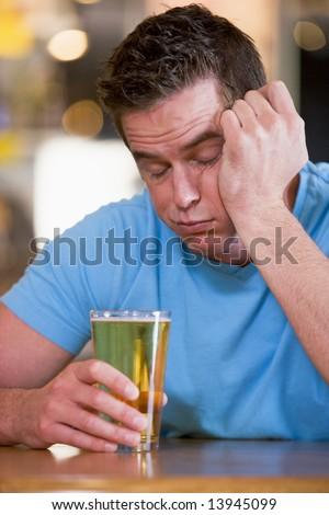 Young man with beer falling asleep at bar - stock photo
