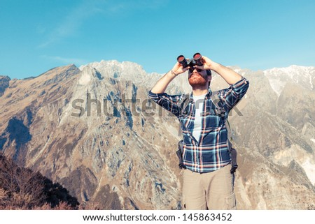Young Man with Binocular at Mountain - stock photo