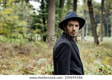 young man with black hat walking in forest