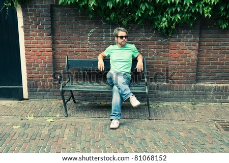 Young man with blond hair wearing sunglasses sitting outside on a bench on summer day. - stock photo