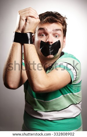 Young man with bonded mouth and hands by black duct tape - stock photo