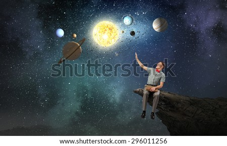 Young man with book exploring planets of sun system - stock photo