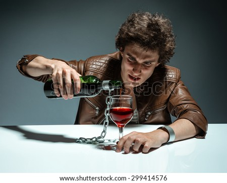 Young man with bottle of alcohol / photo of youth addicted to alcohol, alcoholism concept, social problem - stock photo