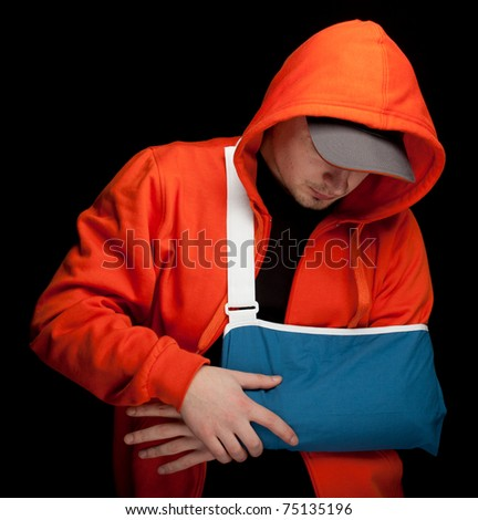 young man with broken hand wearing an arm brace - stock photo