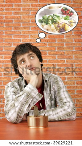 Young man with canned food dreams about real one (in a comic bubble is my other stock photo) - stock photo