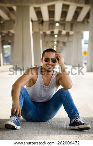 Young man with casual wear sitting in urban background - stock photo