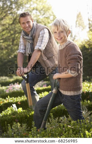 Young man with child working in garden - stock photo