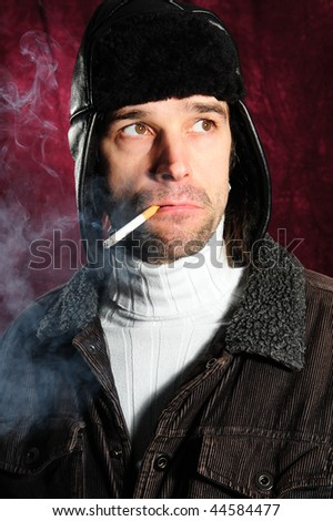 young man with cigarette and coat cap