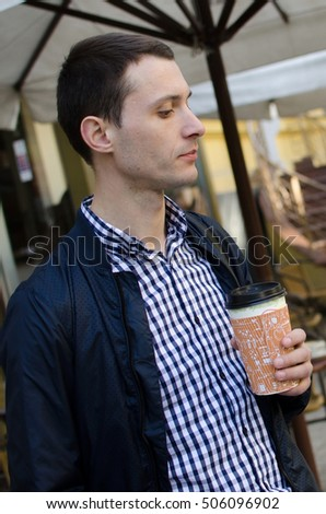 Young man with coffee in the plastic cup on the street