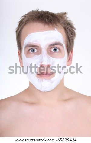 young man with cosmetic mask on his face over white - stock photo