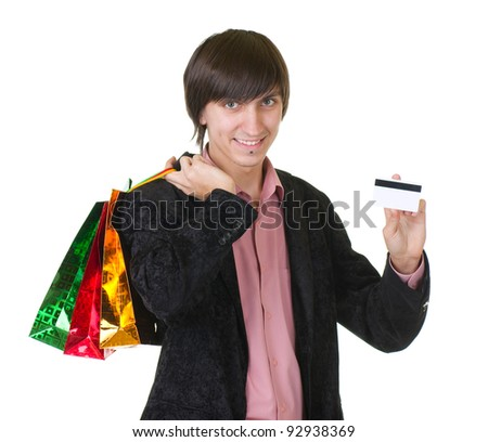 Young man with credit card and shopping bags isolated on white background - stock photo