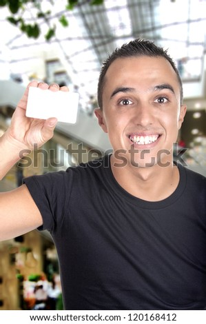 Young Man with credit card in a shopping center - stock photo
