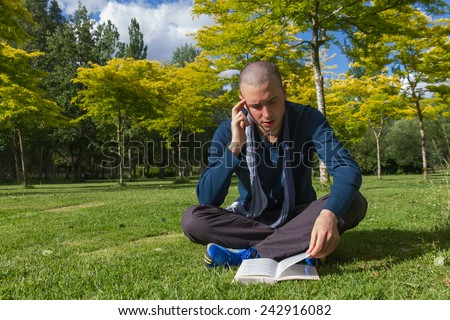 Young man with cropped hair sitting on the grass in a park cross legged and reading a thoughtful book  - stock photo
