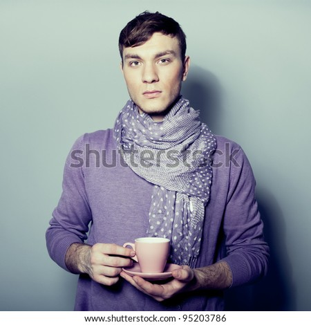 Young man with cup of coffee in his hands