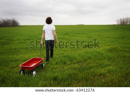Young man with curly hair, pulling a wagon through an open field.