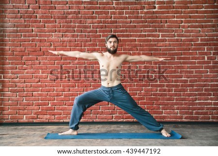 Young man with dark hair and beard wearing trousers doing yoga warrior position on blue matt at wall background, copy space, portrait, virabhadrasana. - stock photo