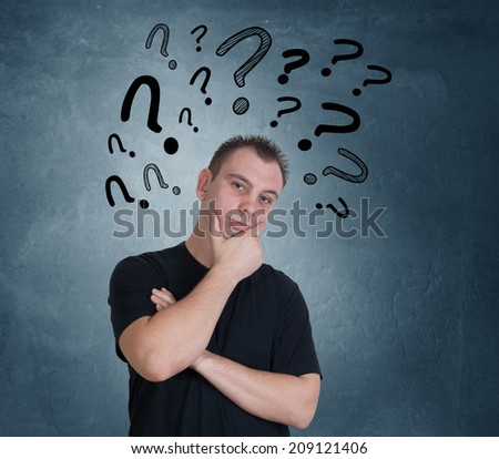Young man with drawn question marks above his head - stock photo