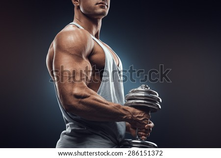 Young man with dumbbell prepare to flexing muscles over dark background. Strong athlete in activewear ready to doing exercise with dumbbell, confidently looking forward. - stock photo