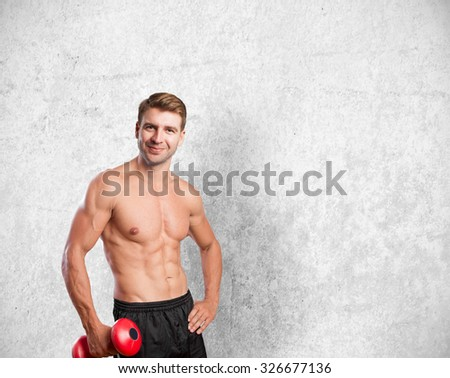 young man with dumbbell strong pose