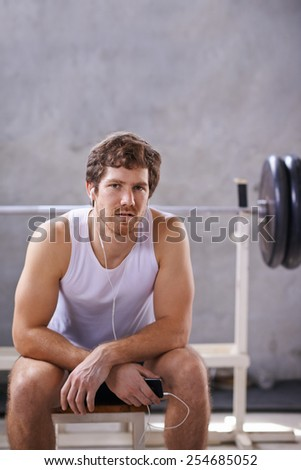 Young man with earphones sitting his private gym ready for a session - stock photo