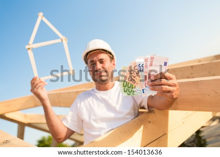 Young man with Euro banknotes and a symbolic house in his hands - stock photo