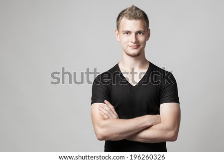 young man with folded arms isolated on light background - stock photo
