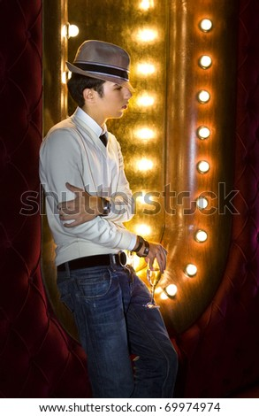 young man with glass of wine near the mirror in cabaret - stock photo