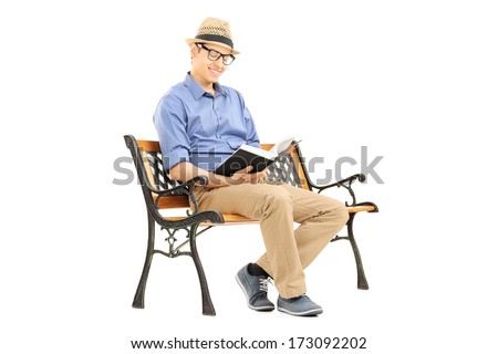 Young man with glasses reading a book on wooden bench isolated on white background