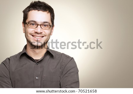 Young man with glasses smiling - stock photo