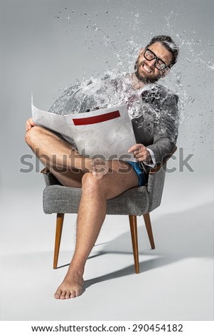 Young man with glasses with bare feet reading newspaper, sitting in the armchair on gray background. He grimaced at the flow of water that is poured on it from a newspaper. the concept of negative - stock photo