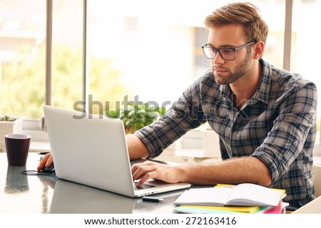 Young man with glasses working on his notebook, with a fresh cup of coffee nice and early in the morning, getting the business out of the way nice and early in the day - stock photo