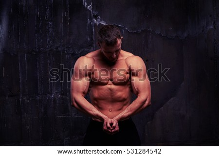 Young man with great physique is standing shirtless and looking at his pumped biceps