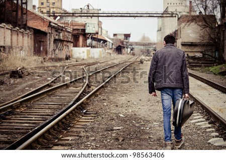 Young man with guitar case in hand is going away among industrial ruins - stock photo