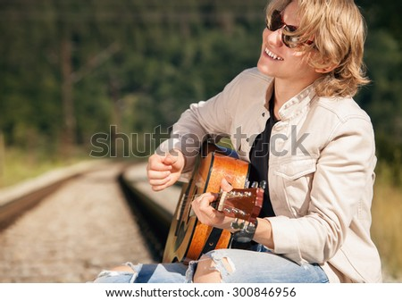 Young man with guitar on the railway - stock photo
