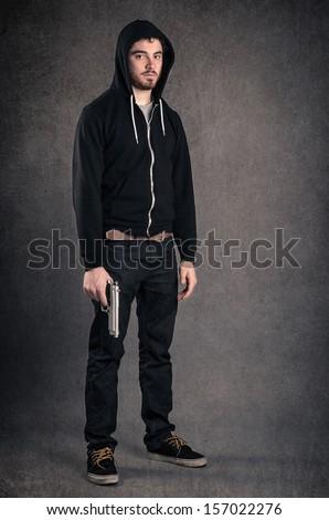 Young man with gun portrait over dark grunge background. Full body.  - stock photo