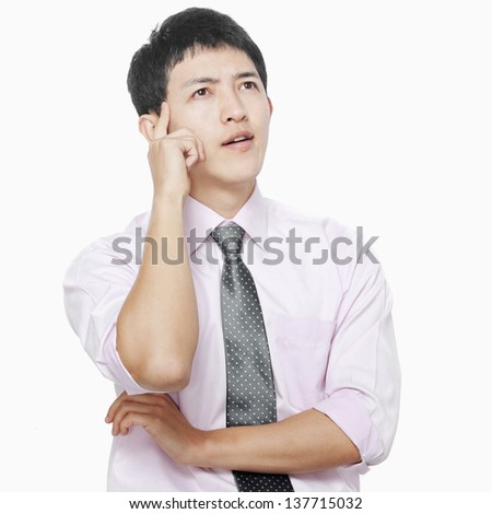 Young man with hand on face thinking