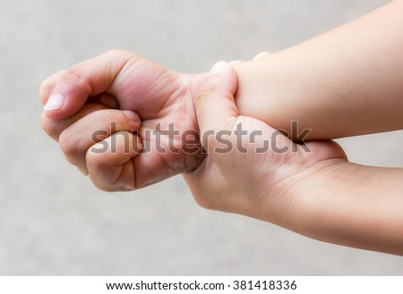 Young man with hand pain - pain concept