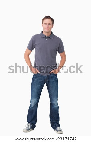 Young man with hands in his pockets against a white background - stock photo