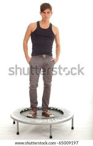 young man  with hands in pockets standing on trampoline