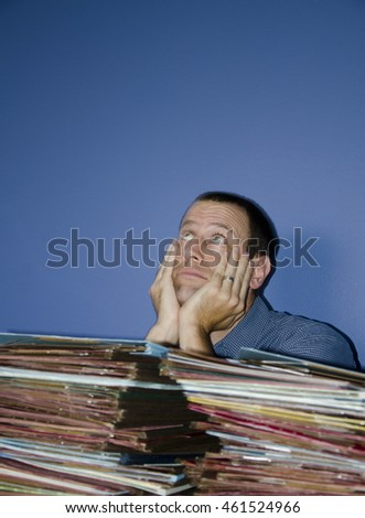 Young man with hands on face behind piles of files and eyes looking up to the ceiling.